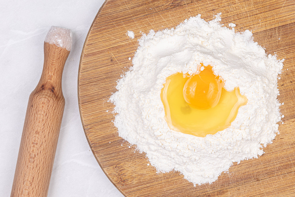 Egg on the top of the flour with wooden rolling pin
