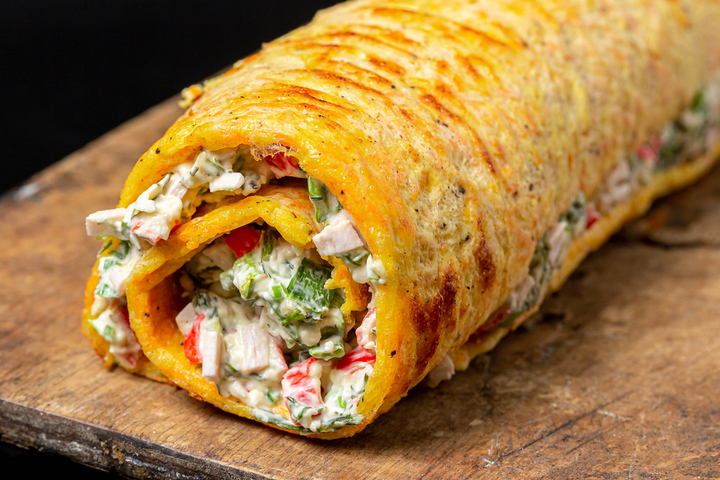 Egg roll with crab meat, herbs and cheese, close-up