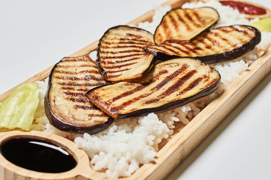 Eggplant grilled with rice on a wooden plate
