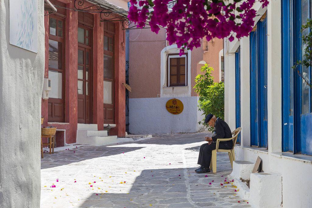 Ein alter Mann sitzt alleine in einer bunten Gasse von Chalki, Örtchen im zentralen Hochland von Naxos