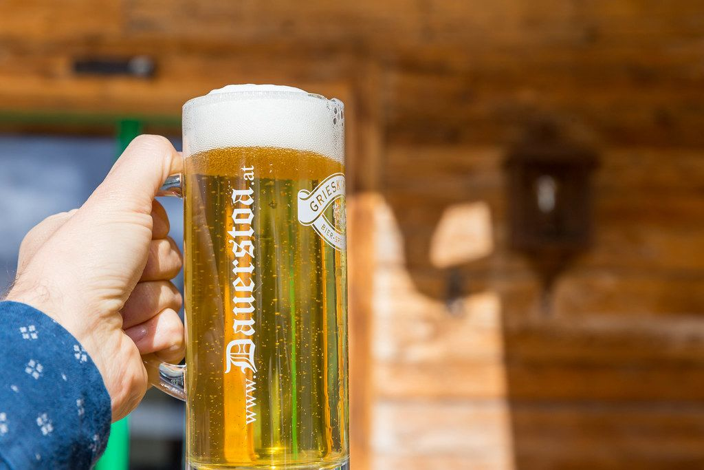 Ein Bier vom Fass bei der Dauerstoa Alm in Alpbach. Nahaufnahme vor hölzernem Hintergrund