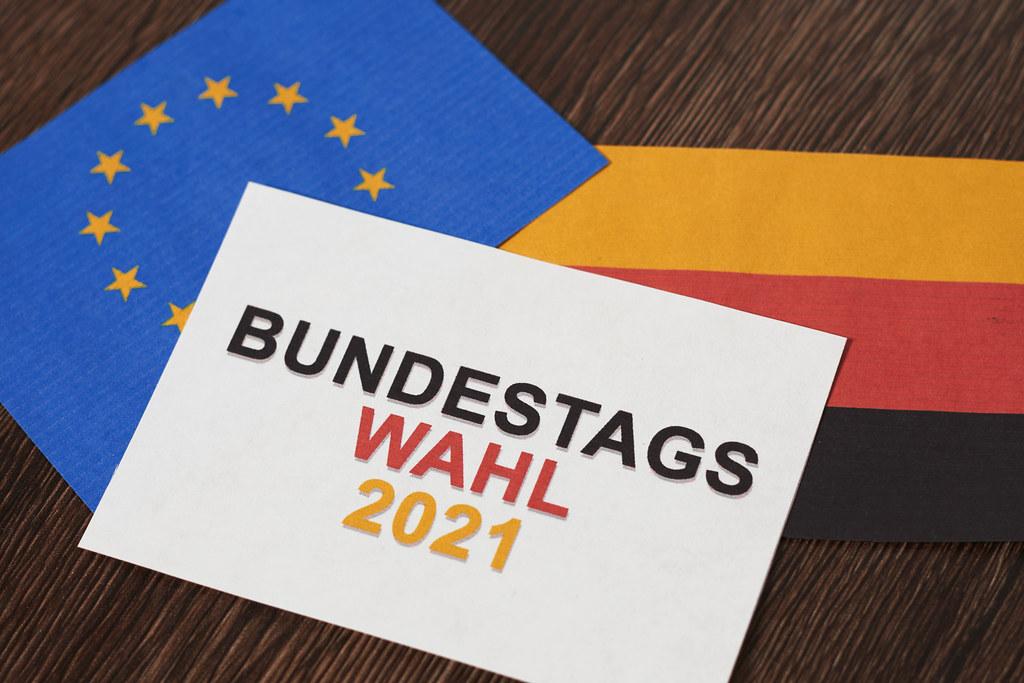 """Ein Blatt mit Schrift """"Bundestagswahl 2021"""" in den deutschen Farben, europäische und deutsche Flagge"""