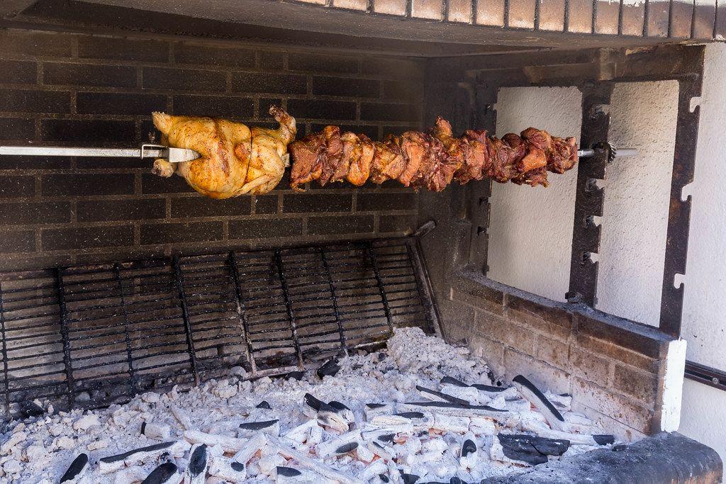 Ein Drehspieß über einer Feuerstelle mit diversen Fleischsorten im griechischen Stil in Chalkio, Naxos