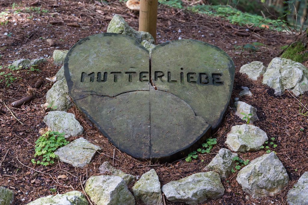 """Ein großes Herz aus Holz mit der Schrift """"Mutterliebe"""" auf dem Boden im Wald in Alpbach"""