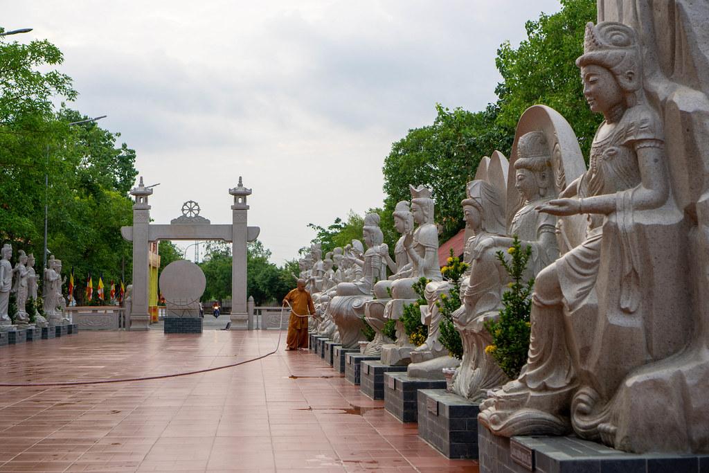 Ein Mönch wässert Pflanzen auf einem Platz mit verschiedenen Lady Buddha Statuen bei der Truc Lam Phuong Nam Pagode in Can Tho, Vietnam