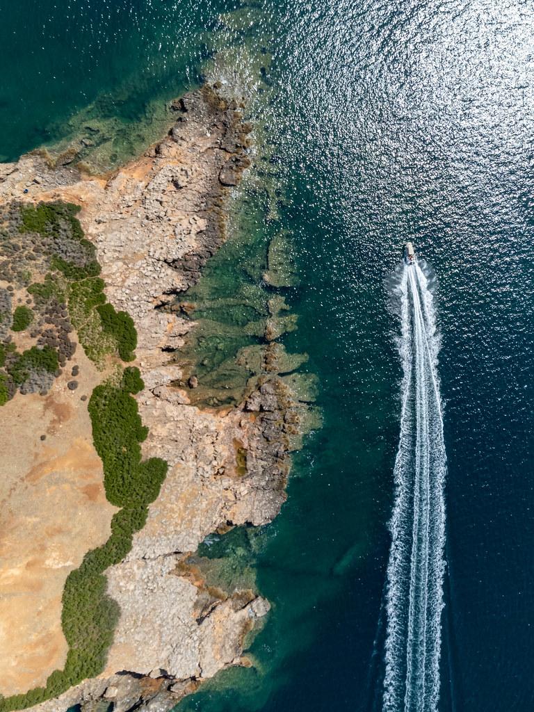 Ein Motorboot fährt an der rauen Küstenlinie der kleinen rötlichen Insel Kokkinonisi entlang