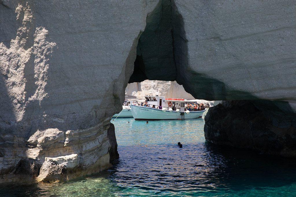 Ein Naturbogen an der Küste der griechischen Insel Milos rahmt ein Boot mit Touristen ein
