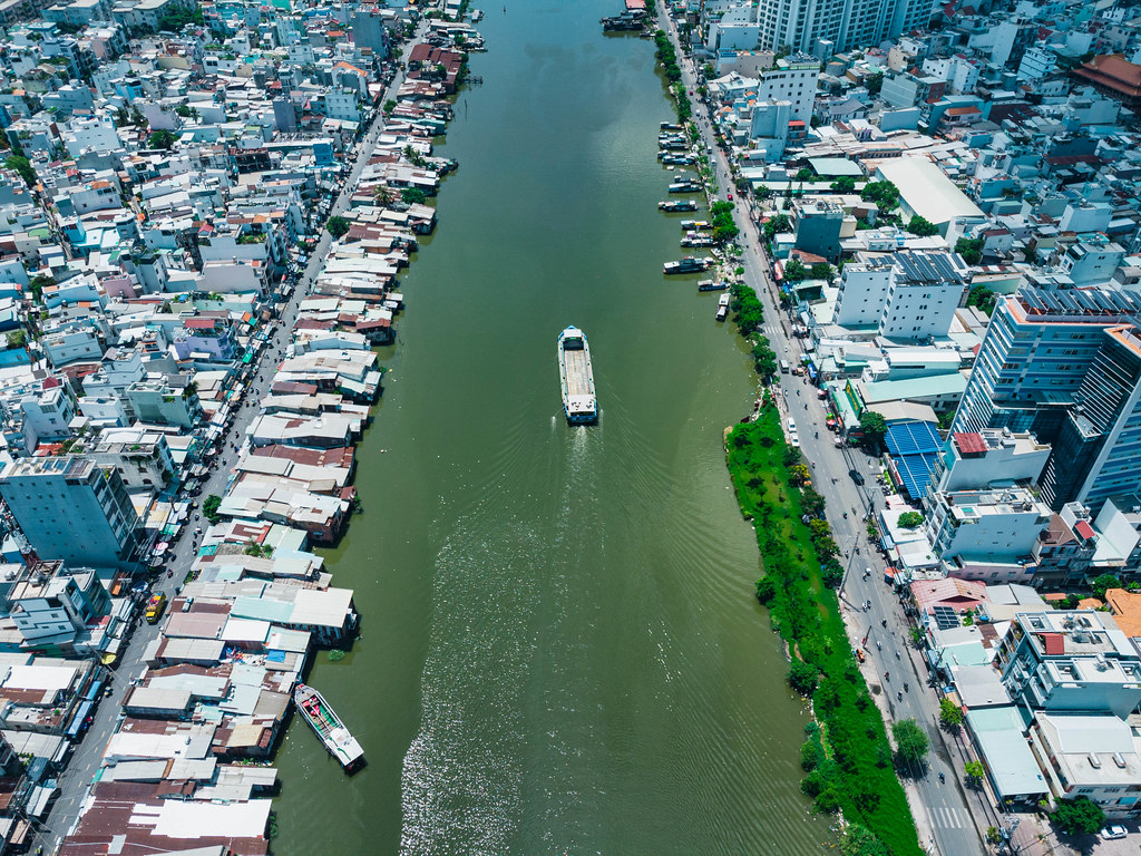 Ein Schiff und kleinere Boote auf dem Saigon Fluss zwischen Distrikt 4 und Distrikt 7 in der Vogelperspektive mit einer Drohne fotografiert in Ho Chi Minh Stadt, Vietnam