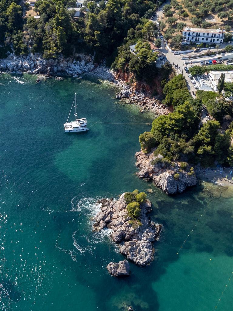Ein Segelboot im türkisblauen Meer Stafylos auf Skopelos: Drohnenaufnahme von der Felsküste