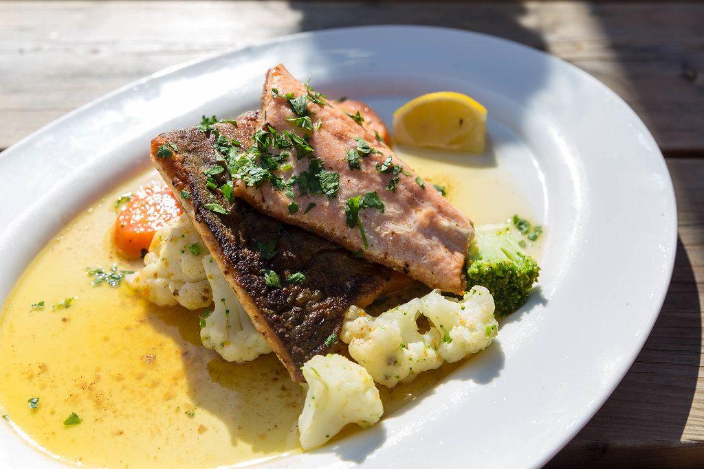 Ein weißer Teller mit Saibling, Blumenkohl, Brokkoli und Kräuter. Typischer Fisch von den Seen der Alpen