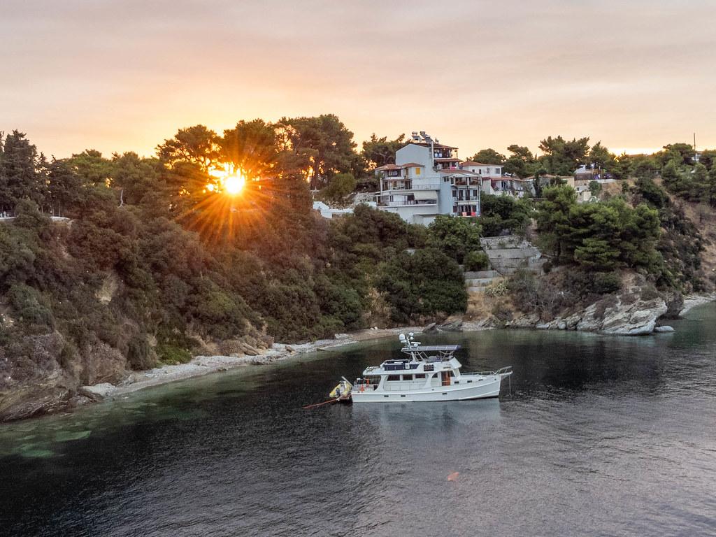 Ein weißes Boot ruht vor den Häusern von Skiathos, Thessalien, bei Sonnenuntergang