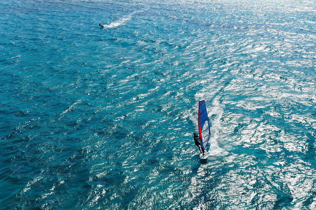Ein Windsurfer und ein Kitesurfer im blauen Meer von Mikri Vigla, Naxos, Griechenland. Drohnenfoto
