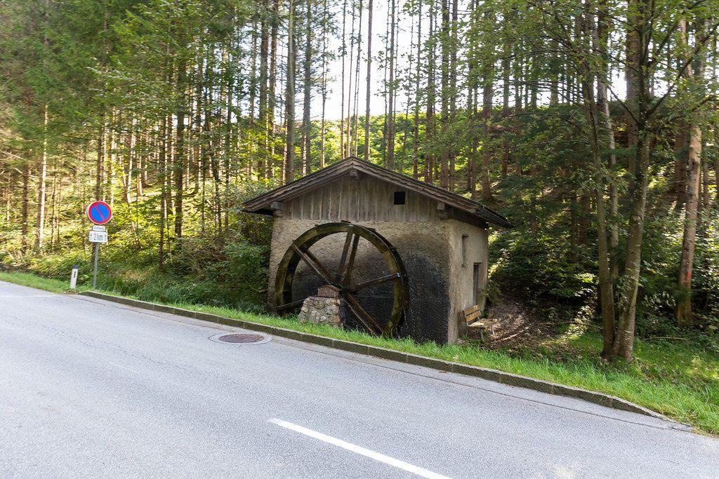 Eine funktionierende Wassermühle mit Wasserrad am Straßenrand in Tirol (Österreich)