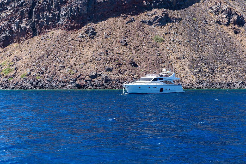Eine Jacht, das Meer und die steile vulkanische Küste Santorinis