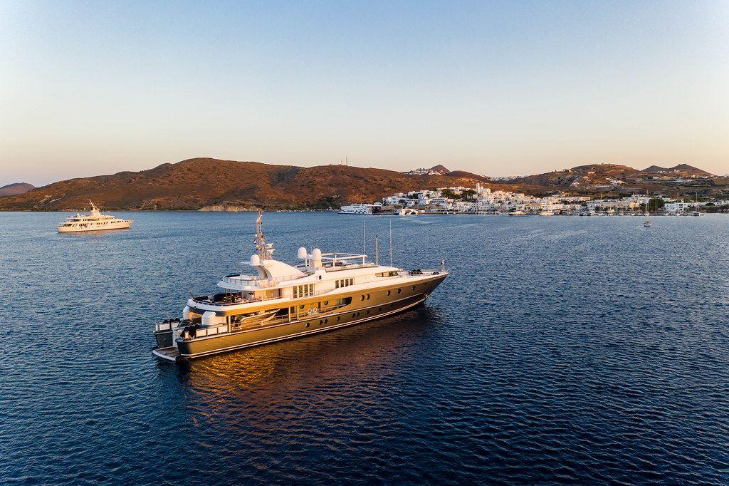 Eine Jacht fährt Richtung Hafen am Sonnenuntergang auf Milos, Griechenland