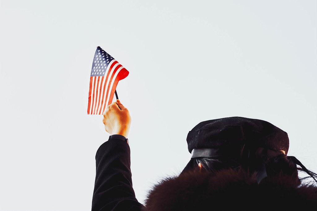 Eine Person in Schwarz angezogen hält eine amerikanische Fahne hoch vor weißem Hintergrund