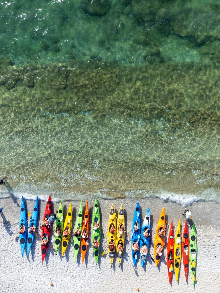 Eine Reihe von Kajaks in verschiedenen Farben am Strand von Milia, Skopelos. Luftbild
