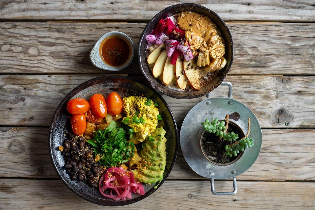 Eine Schüssel mit Porridge, frischen Früchten und Erdnussbutter und ein Teller mit Tofu, Avocado, Kartoffeln und schwarzen Bohnen von oben auf einem Holztisch fotografiert