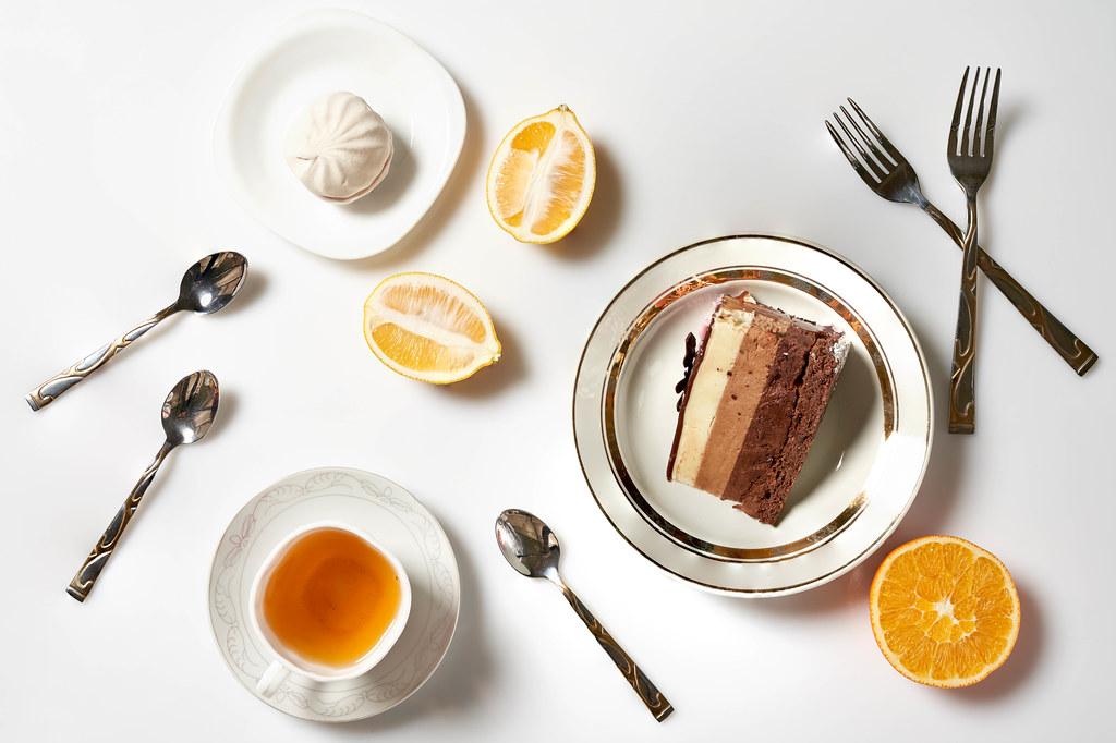 Eine Tasse Tee mit Torte auf dem Teller serviert. Aufnahme von oben mit Besteck, Zitrone, Orange