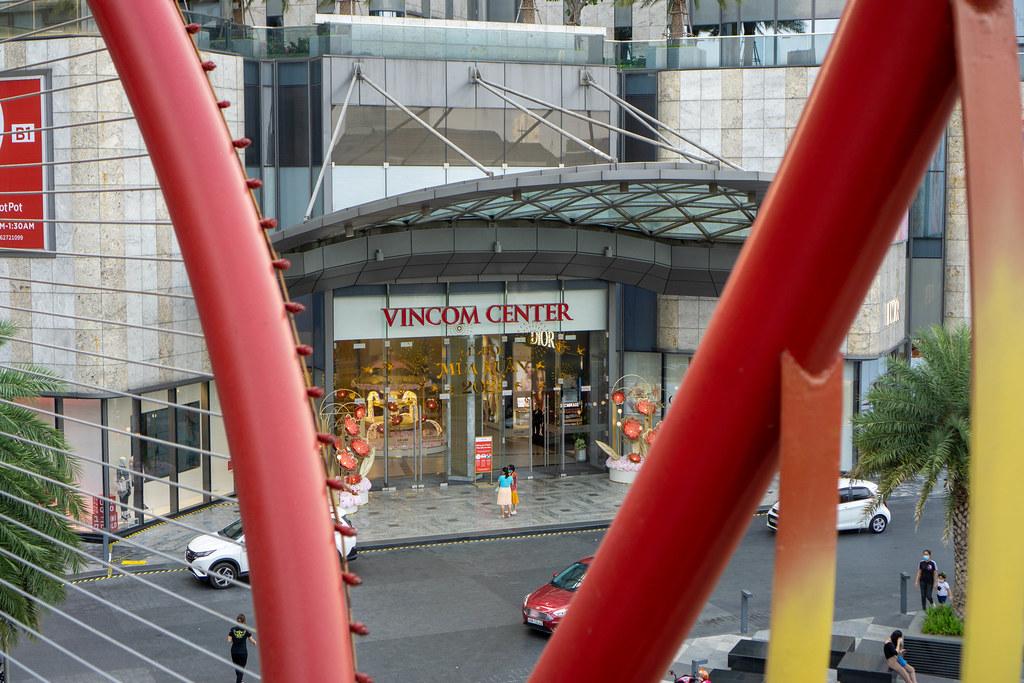 Eingang des Vincom Center Einkaufszentrums am Landmark 81 Wolkenkratzer von einer Fußgängerbrücke aus fotografiert in Ho Chi Minh Stadt, Vietnam
