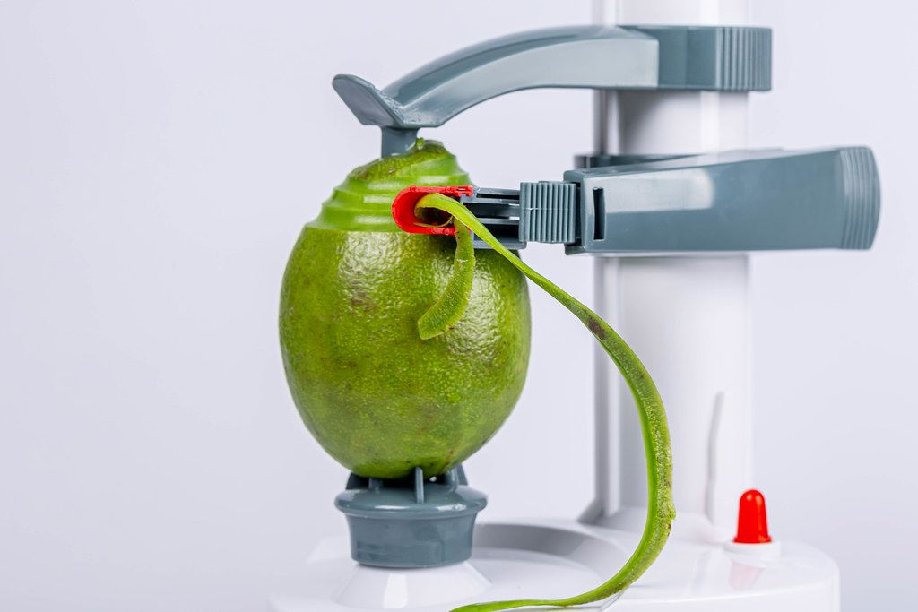 Electric fruit and vegetable peeling machine removes the skin from the avocado