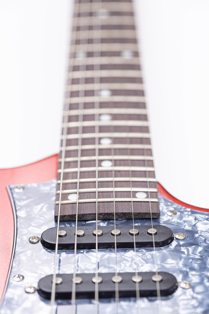 Electric Guitar and Neck with Frets above white background