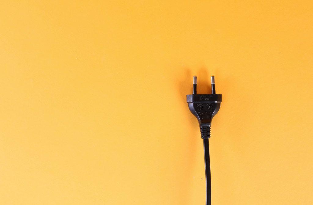 Electric plug on orange background