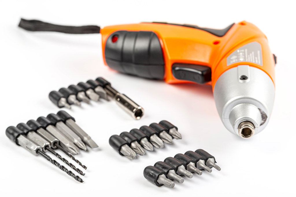Electric screwdriver on white background with bits and drills