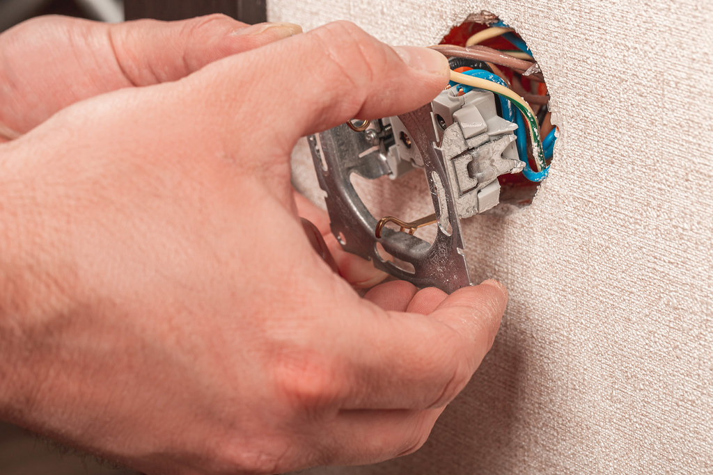 Electrician installing electrical socket on wall