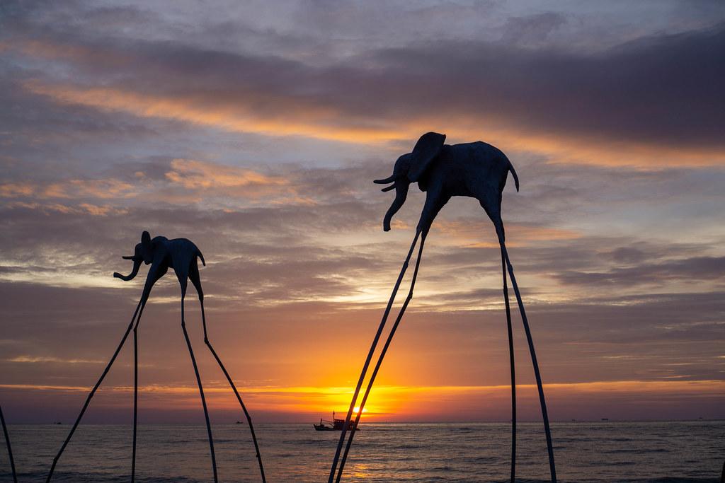 Elefanten auf Stelzen als Touristenattraktion am Sunset Sanato Beach Club bei Sonnenuntergang mit Fischerboot im Hintergrund in Phu Quoc, Vietnam