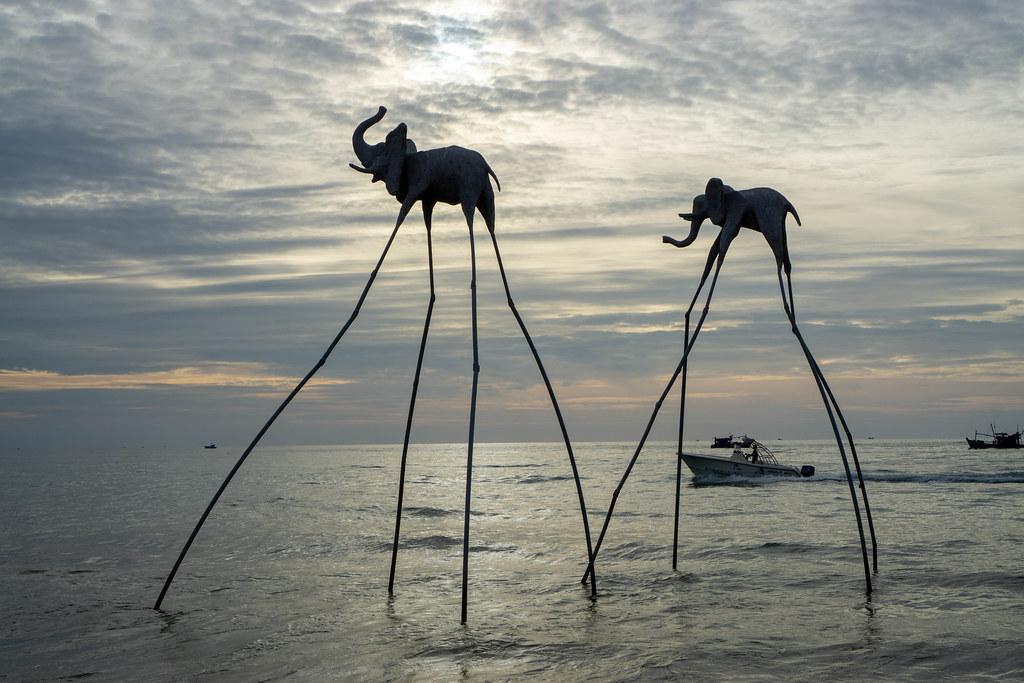 Elefanten Skulpturen auf langen Stelzen im Meer mit Fischerbooten und Motorboot im Hintergrund bei Sonnenuntergang in Phu Quoc, Vietnam