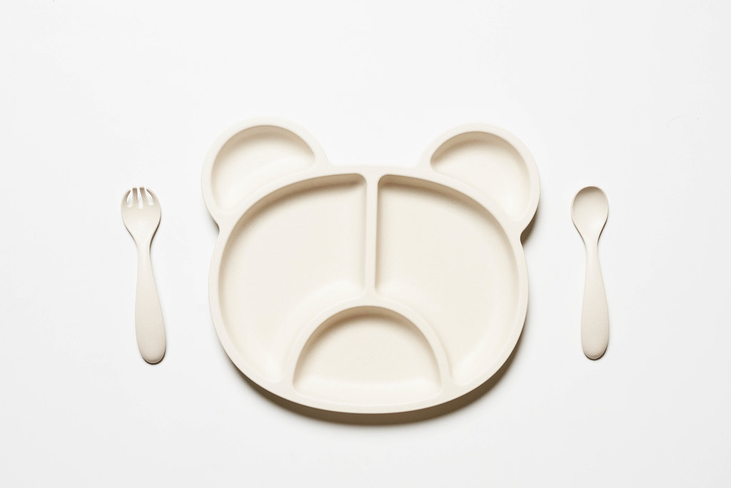 Empty eco-friendly bamboo plate in shape of bear and white spoon and fork