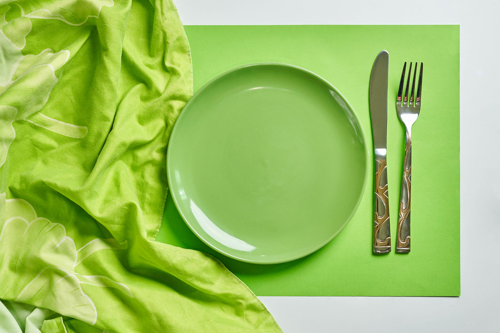 Empty green plate with spoon and fork