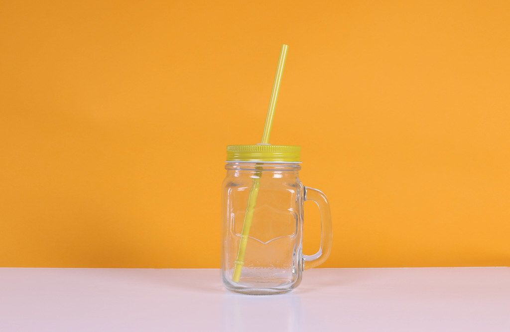 Empty mason jar on orange background