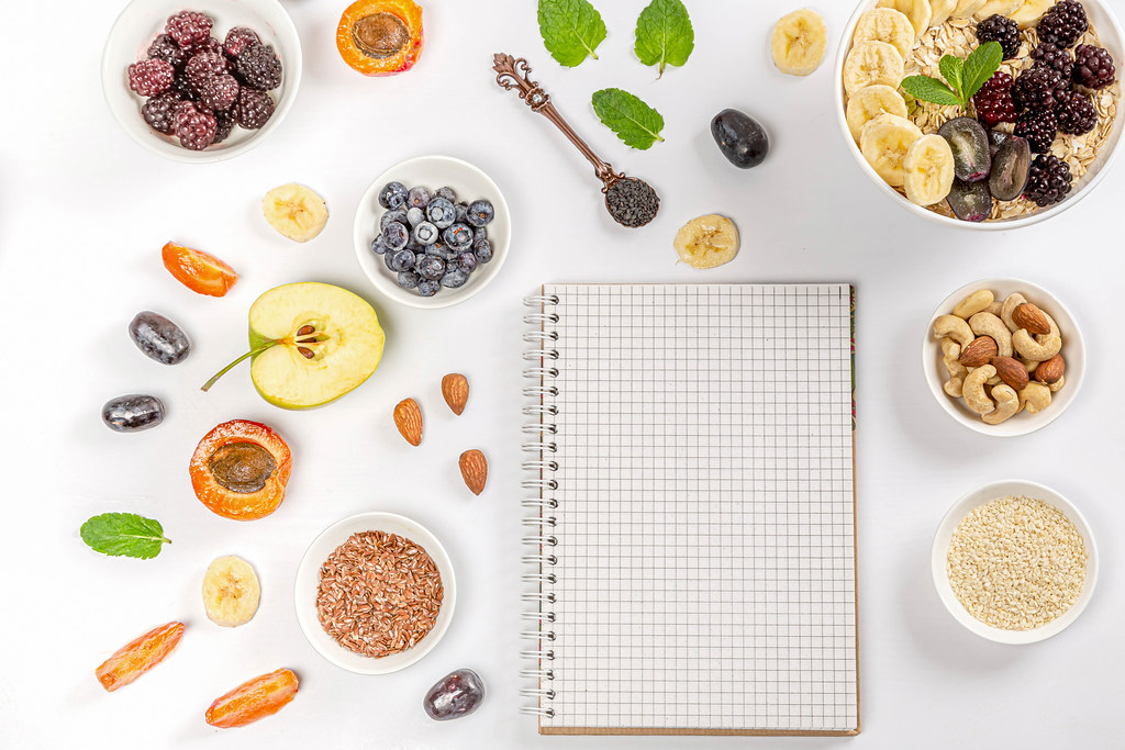 Empty notebook with healthy food ingredients, top view