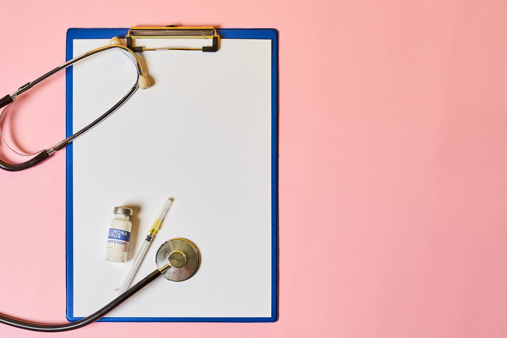 Empty paper with a stethoscope and covid vaccine