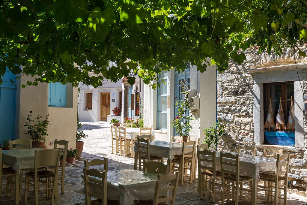 Empty restaurant tables in the shade on a quiet side street of Halki, picturesque tiny village on Naxos