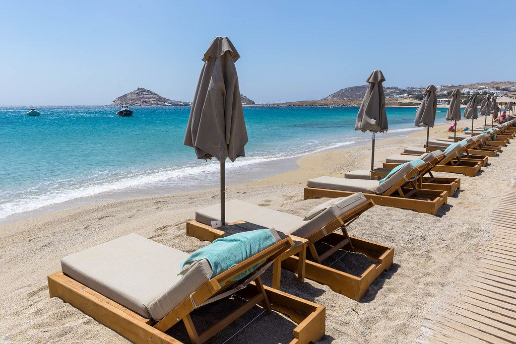 Empty sun beds and closed beach umbrellas. Holiday in summer 2020 at Kalafati beach, Mykonos