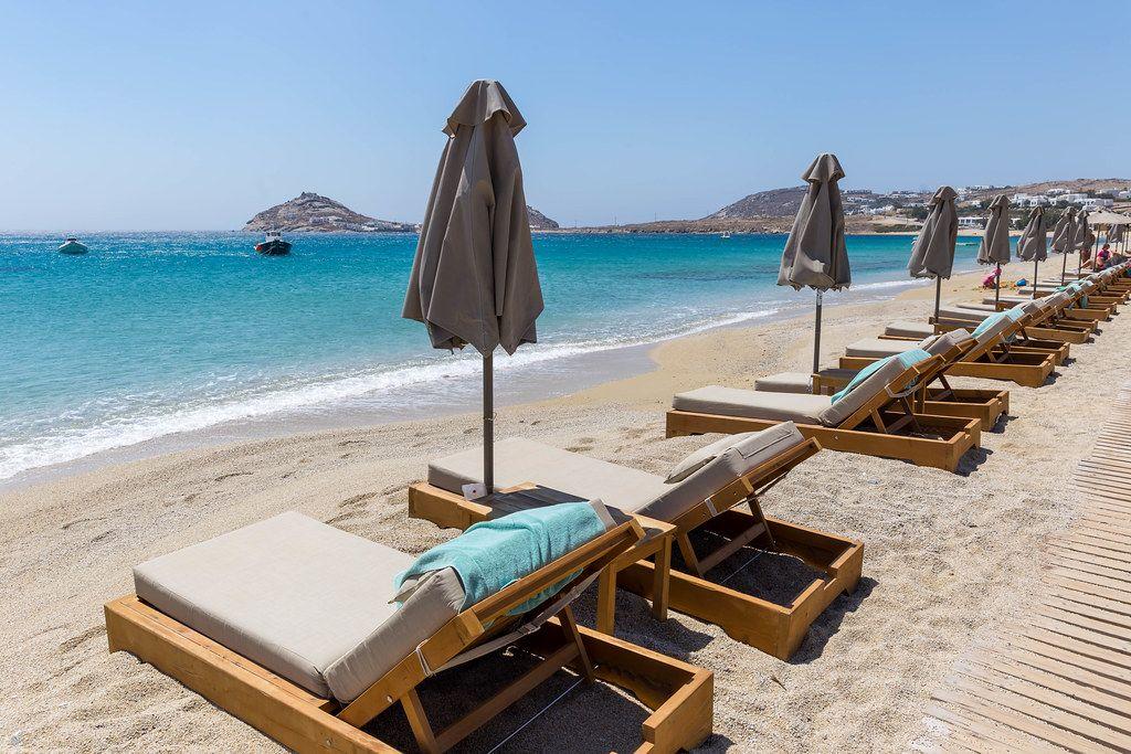 Empty sun beds and closed beach umbrellas. Holiday in summer 2020 at Kalafati beach, Mykonos