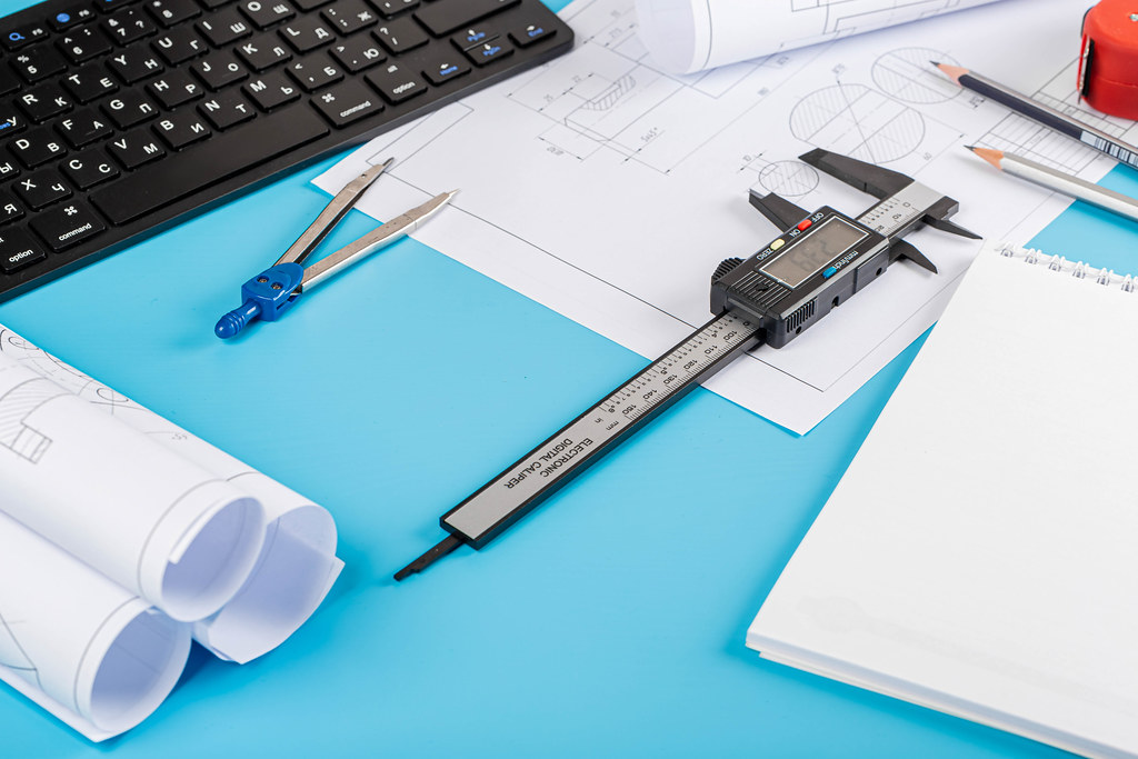 Engineer workplace concept with tools and drawings on blue background