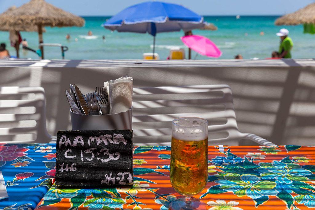 Erfrischung am Strand. Bier vom Fass, Reservierungsschild und Besteck auf dem Tisch