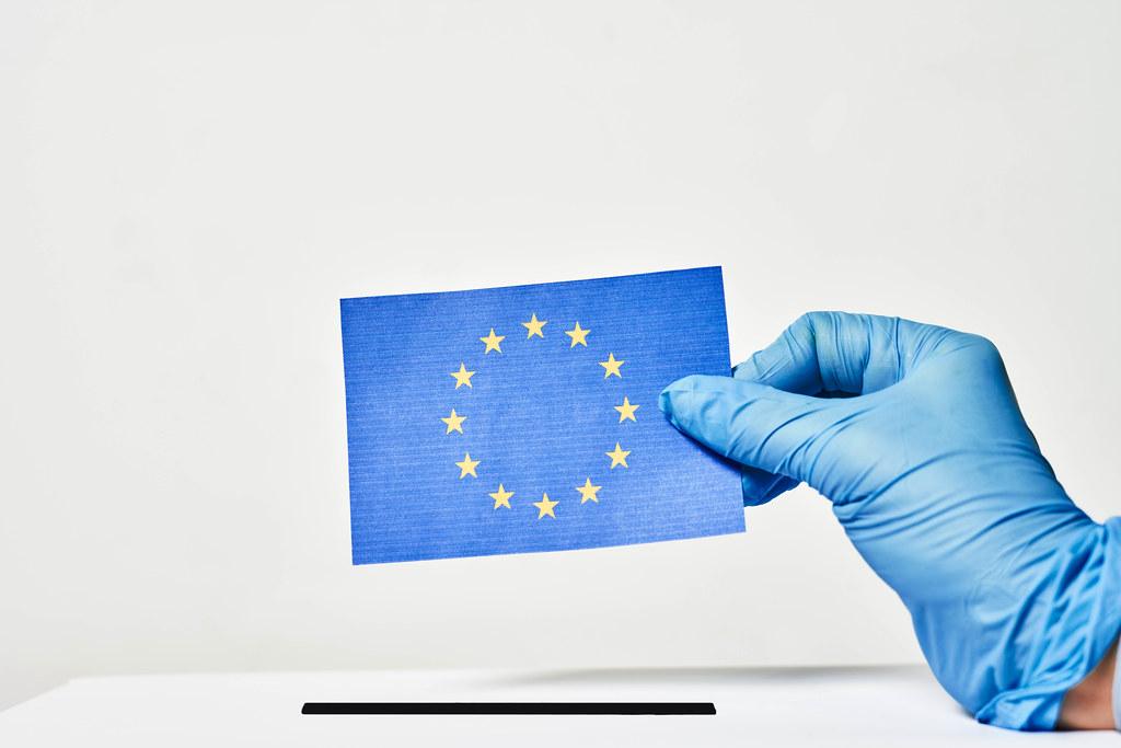 Europa, Wahl und Covid-19: Hand mit Einweghandschuh wirft EU-Zettel in die Wahlurne ein
