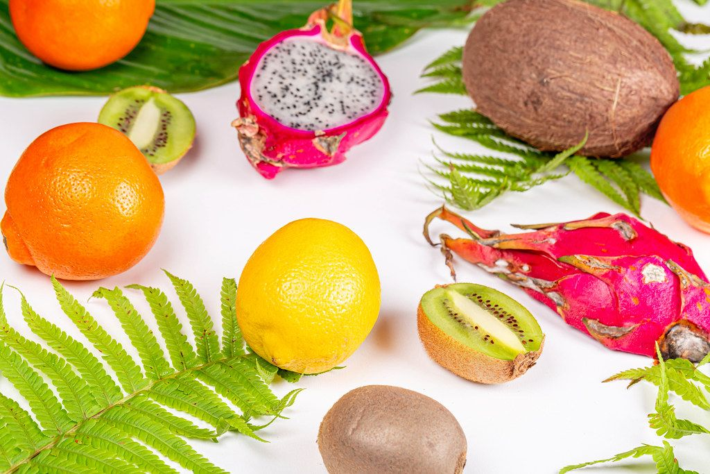 Exotic fruits on white background with green leaves
