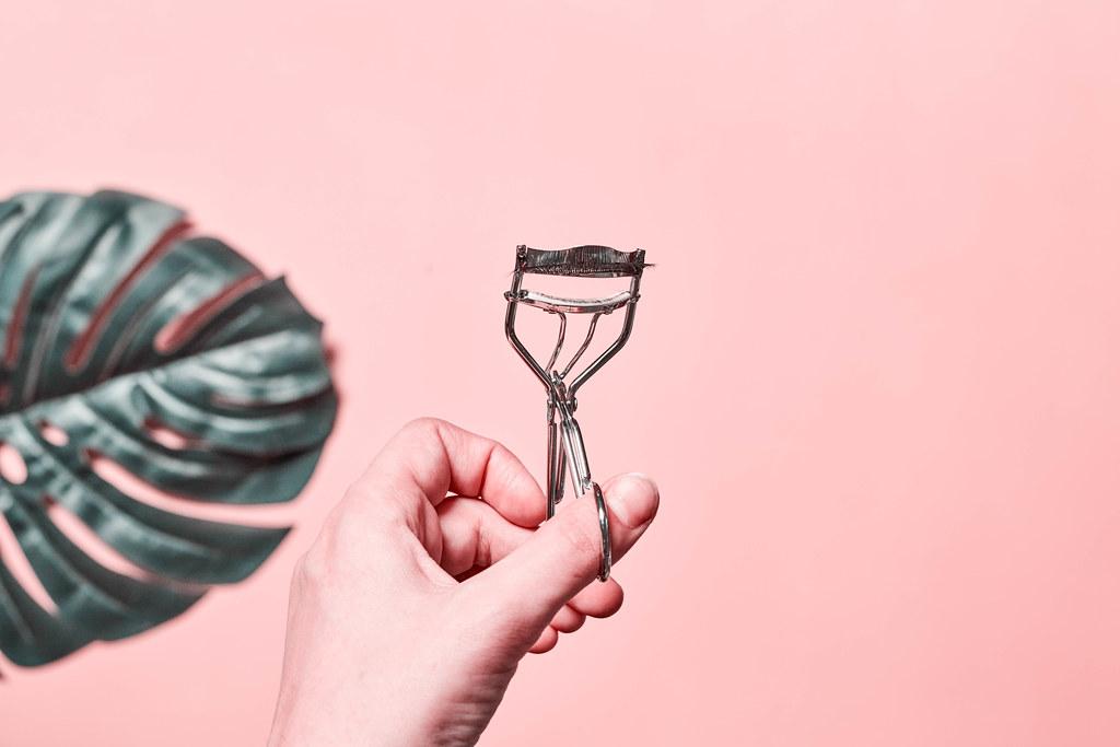 Eyelash curler in female hands