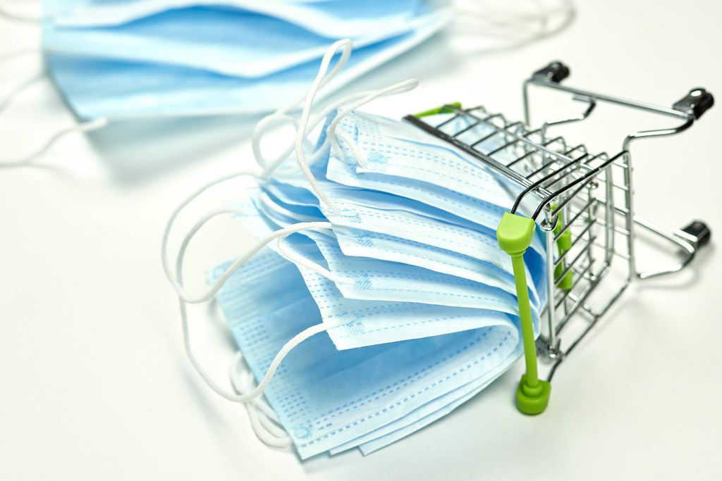 Face masks deficit concept - stack of surgical masks in shopping trolley