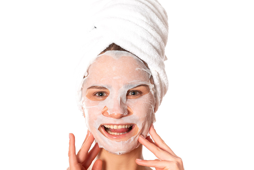 Face of smiling girl with cosmetic cloth mask
