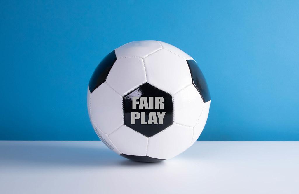 Fair Play text on a soccer ball with blue background