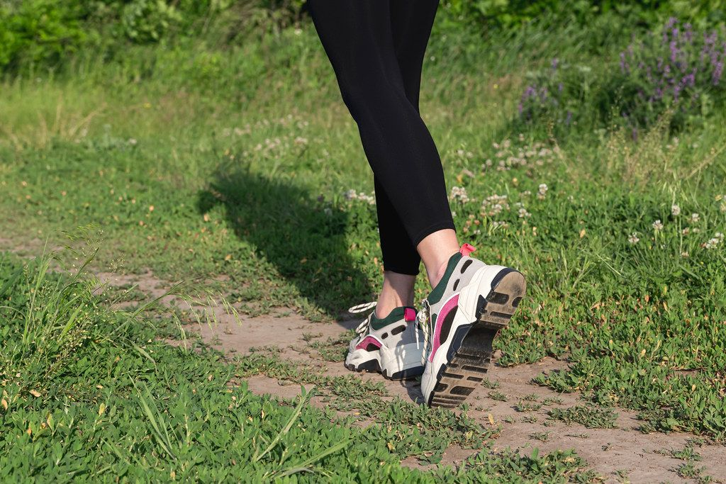 Feet of a girl running along a path in summer