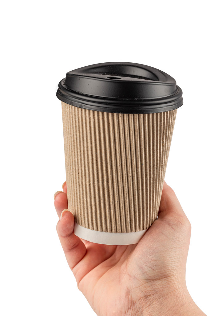 Female hand holding a coffee paper cup