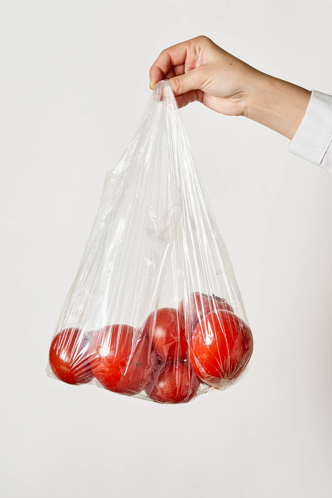 Female hand holding a transparent bag with tomatoes
